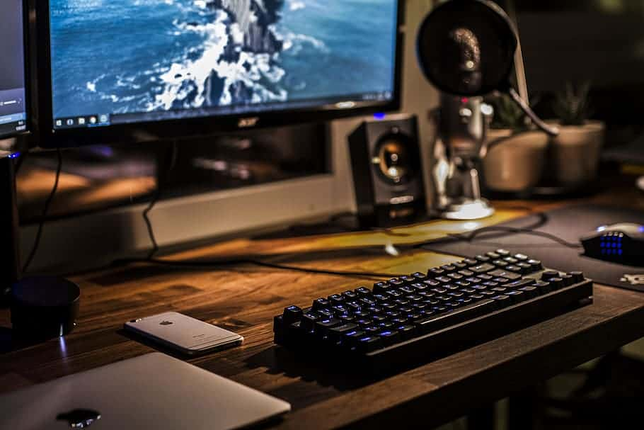 Wood deck with mechnical keyboard, speakers and a gaming monitor for gaming