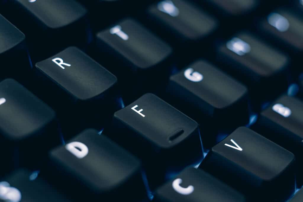 Macro photo of mechanical keyboard. Focus on the letter R and F keys. The letters are etched on black plastic keycaps to reveal the led backlight. Other keys are out of focus in the background.